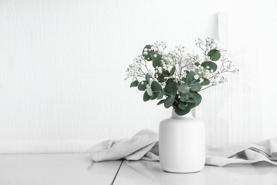 Vase with beautiful bouquet on table in kitchen