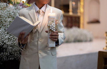 First communion ceremony in church bible and candle