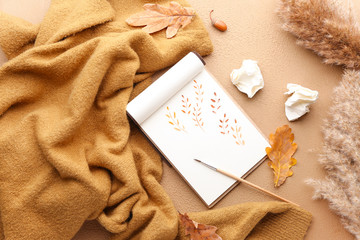 Beautiful autumn composition with sweater, notebook, brush and leaves on color background