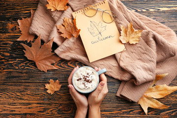 Female hands with hot chocolate in cup, warm sweater and dry leaves on wooden background