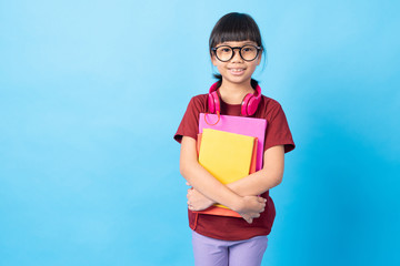 Graduate and education concept, Asia Thai girl kid student holding books and earphone on blue background in studio