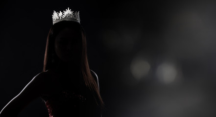 Portrait of Miss Pageant Beauty Contest in sequin Evening Ball Gown long dress with sparkle light Diamond Crown, silhouette low key exposure with curtain, studio lighting dark background dramatic