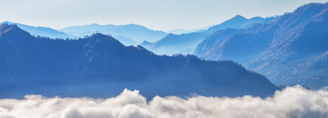 Wall Mural - Panoramic view of the mountains. Beautiful morning view. Blue peaks rise above the clouds.