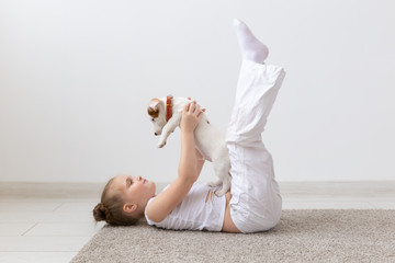 people, children and pets concept - little kid girl lying on the floor with cute puppy in hands