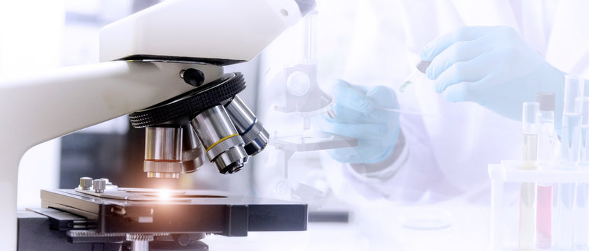 Laboratory concept:  Close up picture of microscope with blurred background of scientist preparing the sample for testing in laboratory.