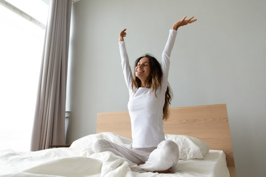 Energetic positive young mixed race lady stretching body.