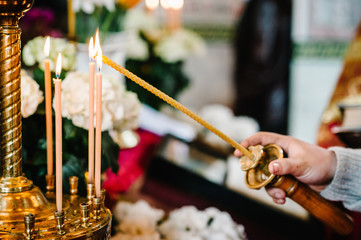 The priest's hand lights a candle near the candlestick in the church.