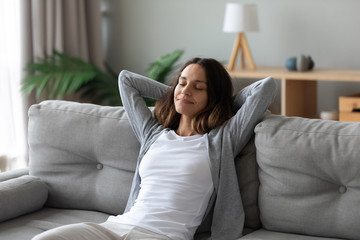 Tranquil smiling biracial millennial woman leaning on sofa.