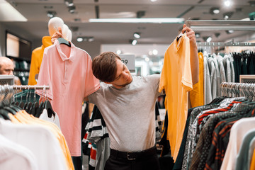 it's shopping time. young man in the casual clothes store