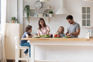 Happy family with little children preparing salad together