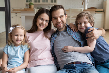 Portrait happy family, parents with little kids hugging at home