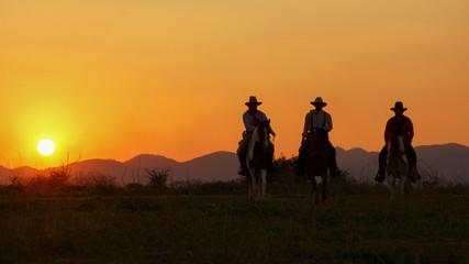 Three of Cowboys riding horses at sunset.