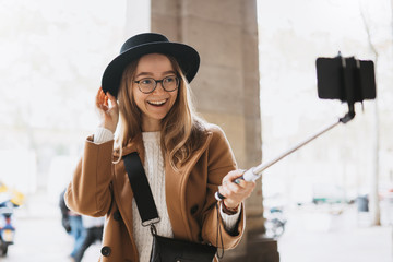 Smiling tourist girl taking photo selfie on smartphone mobile. Blogger hipster travels in Barcelona. Holiday concept in street. Traveler in glasses and hat self cellphone technology in europe trip