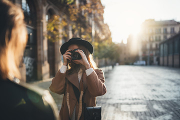 Blogger photoshoot concept. Photographer with camera take photo model girlfriend. Tourist smiling girl travels in Barcelona holiday with traveler friend. Sunlight flare street in europe city