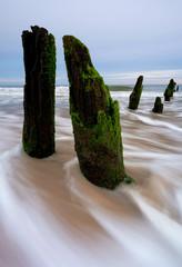Wybrzeże Morza Bałtyckiego,fale oblewają stary falochron.