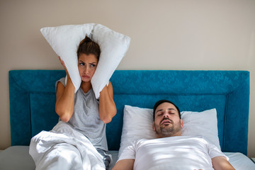 Young couple have problem with man's snoring. Heterosexual couple in bed, man sleeps and snoring with mouth open, while a tired woman irritated by snoring sitting on bed with a pillow on her head.