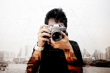 asian man photographer with old camera in city abstract background