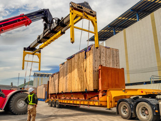 Fototapeta The over high cargo to lifting with the special equipment and control by foreman in yard.