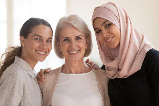 Happy beautiful diverse two generation women bonding looking at camera