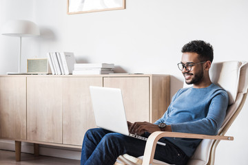 Handsome young man using laptop computer at home. Student men resting in his room. Home work or study, freelance concept