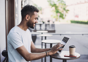 Smiling man student using digital tablet in a city. Young handsome men having coffee break. Modern lifestyle, connection, business, freelance work concept