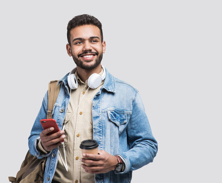 Young handsome man with backpack holding smart phone and coffee. Smiling student going on a travel. Isolated on gray background