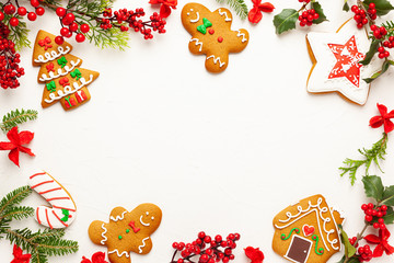 Christmas background with gingerbread cookies and branches of holly with red berries on white....