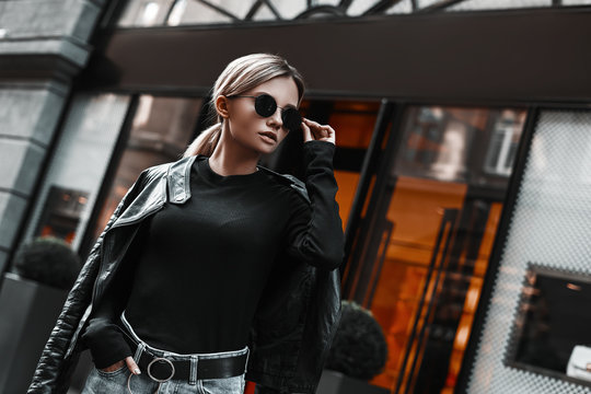 Fashion stylish woman in leather jacket, jeans, sweater and sunglasses walking on road on shops background. Elegant trendy outdoors portrait of pretty girl model on city street