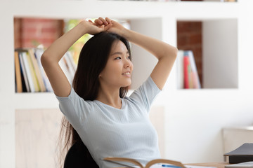 Calm asian student girl sitting at desk resting after study