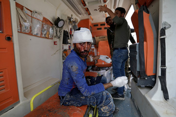 Wounded man looks on as he sits inside an ambulance in the town of Tal Abyad