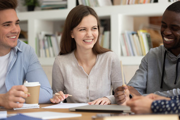 Multi-ethnic students distracted from learning process telling jokes laughing