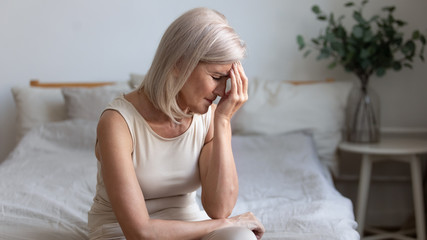 Older woman sit on bed coping with morning headache concept