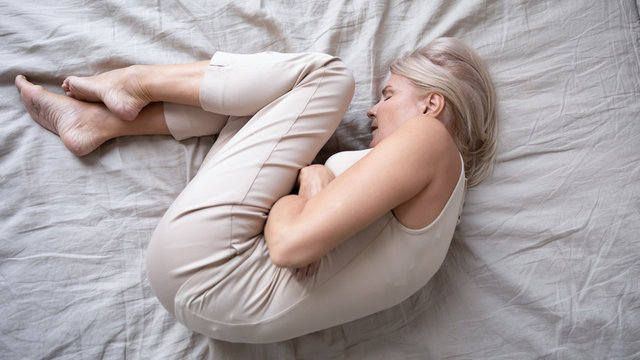 Depressed mature woman lying alone on bed in fetal position