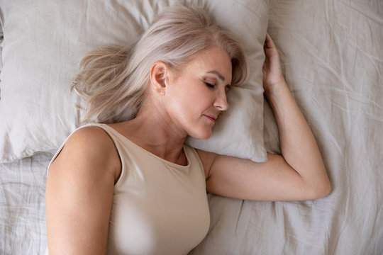 Peaceful healthy mature woman lying asleep in bed, top view