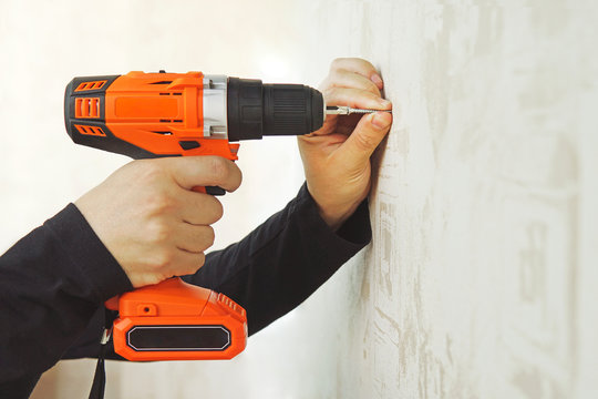 Concept. Worker is screwing the drywall screw by screw gun to the plasterboard wall in apartment is under construction, remodeling, renovation, overhaul, extension, restoration and reconstruction