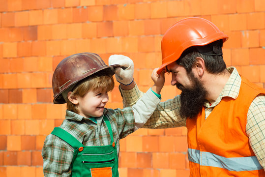 Happy builders. Protective helmets. Occupational Safety and Health. Family at a construction site. Own house. The American dream. Happy family, father and son.