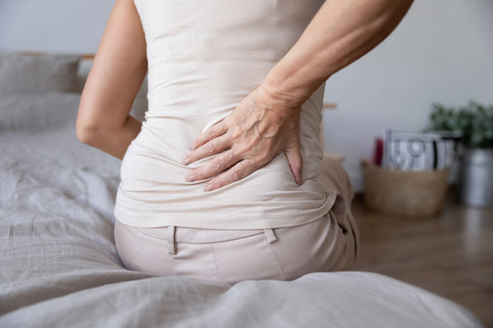 Old mature woman sit on bed touch back feel backpain