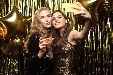 Image of two attractive girls in stylish outfit holding smartphone and taking selfie photo on gold background.