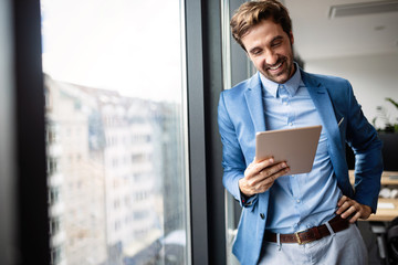 Wall Mural - Portrait of businessman smiling while using digital tablet