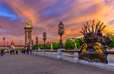 Wall Mural - Pont Alexandre III bridge over river Seine and Hotel des Invalides on background at sunset in Paris, France