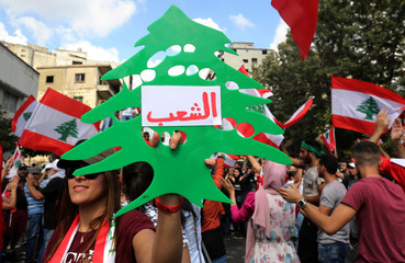 A demonstrator carries a replica of the green cedar tree which is the symbol of Lebanon during an anti-government protest in the southern city of Nabatiyeh