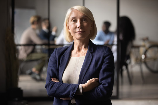 Confident successful mature old businesswoman look at camera in office