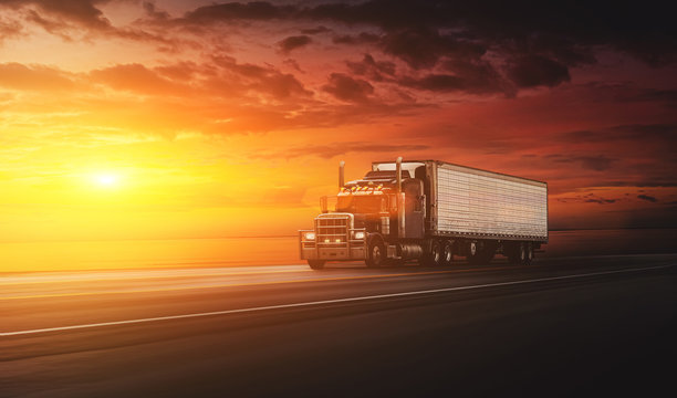 American style truck on freeway pulling load at the sunset. Transportation concept