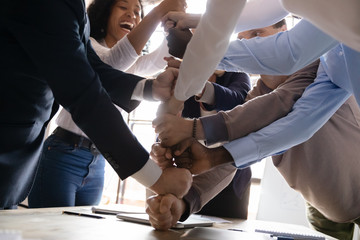 Overjoyed multiracial business team stack fists together, close up view