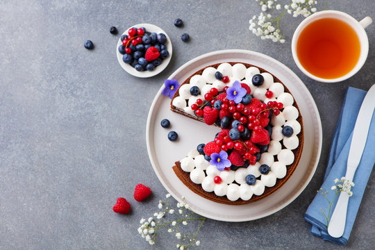Chocolate cake with whipped cream and fresh berries. Grey background. Top view. Copy space.