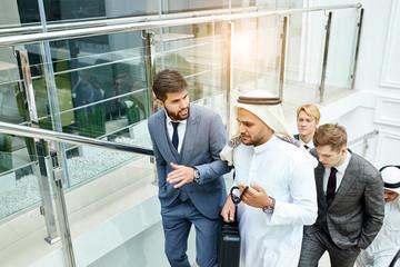 Sheikh holding black case and speak. Rich men make business deal