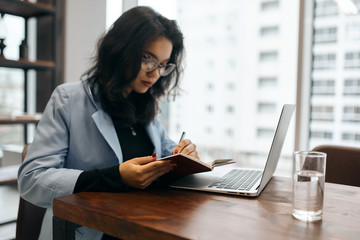 attractive cute office worker writing something on her notepad while sitting at the table in the office with panorama window. close up side view photo. copy space