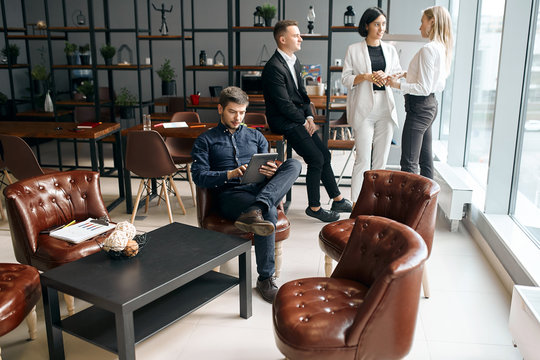 successful young businessman consulting clients online, while his partners brainstorming in the background of the photo. free time, spare time