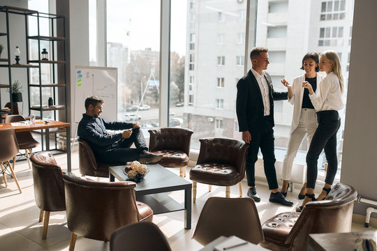 Business people meeting, talking while standing in front of the panorama window, while handsome cheerful man sitting on the armchair and using his tablet. copy space.conversation concept