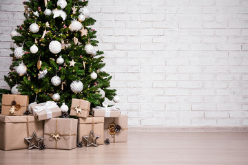 decorated christmas tree and gift boxes over white brick wall with copy space